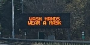 Digital sign by the highway: Wash hands, wear a mask.